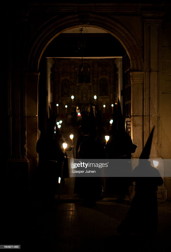 Penitents of the Cofradia del Santisimo Cristo del Silencio y la Expiracion brotherhood enter their church at the end of a holy week procession on March 29, 2013 in Luque near Cordoba, Spain. The origin of this small brotherhood, which uses a skull with crossed shins prominently as their symbol, referring to the mortality and short duration of life but also to the triumph of Jesus over death, dates back to the fifties when a group of young catholic's came up with the idea of forming the brotherhood. Since its founding the brotherhood has a strict penitential character with one of its aims being the public prayer of the Stations of the Cross in the early hours of Good Friday through the streets of this small Andalusian town. Home to the brotherhood is the San Nicolas de Tolentino convent church which was founded in 1626 and dedicated to Our Lady of Grace.