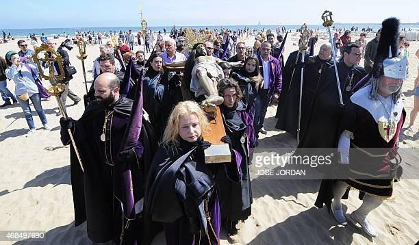 Penitents of the 'Cristo Salvador y del Amparo' brotherhood carry a cross during the Holy Week procession on the beach in Valencia on April...
