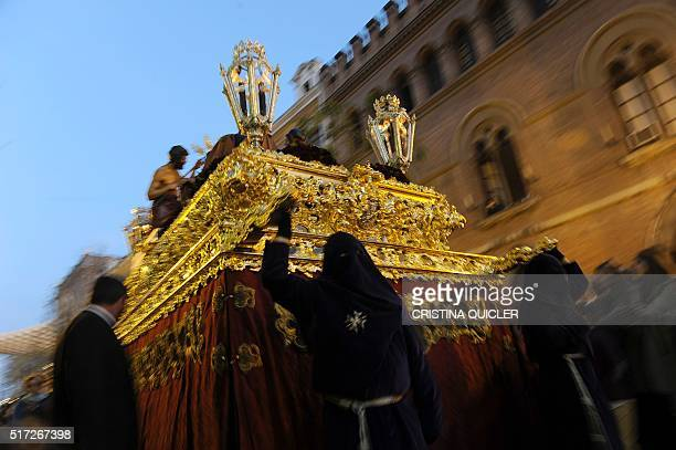 TOPSHOT Penitents of the 'El Valle' brotherhood carry an effigy of the Christ as they parade during an Easter procession in Sevilla on March 24 2016...