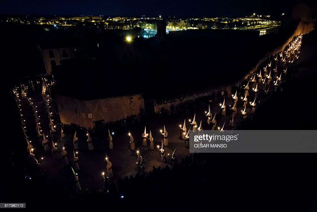 TOPSHOT Penitents of the 'Jesus Yacente' brotherhood hold candles as they parade during a Holy Week procession in the northwestern Spanish city of...