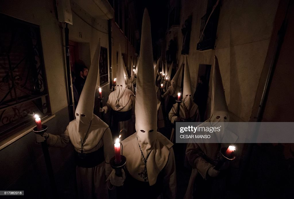 TOPSHOT Penitents of the 'Jesus Yacente' brotherhood hold candles during a Holy Week procession in the northwestern Spanish city of Zamora on March...