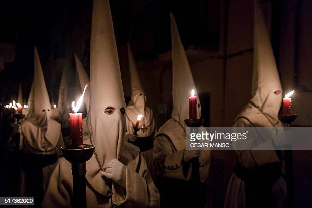 Penitents of the 'Jesus Yacente' brotherhood hold candles during a Holy Week procession in the northwestern Spanish city of Zamora on March 24 2016...