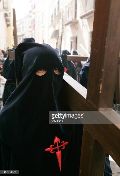 Penitents take part in the La Carretera brotherhood procession during the Holy Week in Sevilla
