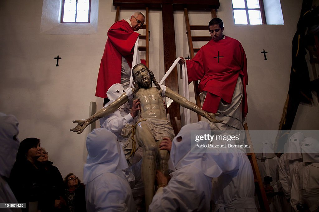 Penitents wearing capirote take down a figure of Jesus Christ from the cross before the start of their Holy Week procession of the Cofradia of Santo Entierro brotherhood on March 29, 2013 in Bercianos de Aliste near Zamora, Spain. The procession was finally stopped because of the rain. Easter week is traditionally celebrated with processions in most Spanish towns.