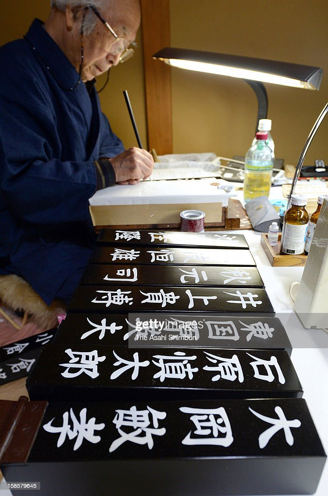 A penman draws names of newly elected lower house lawmakers on the japanned square poles at japan factorage company 'Nushisa Factory' on December 19, 2012 in Tokyo, Japan. The production is in full swing in time for the extraordinary session called on December 26, when new Prime Minister Shinzo Abe officially elected.