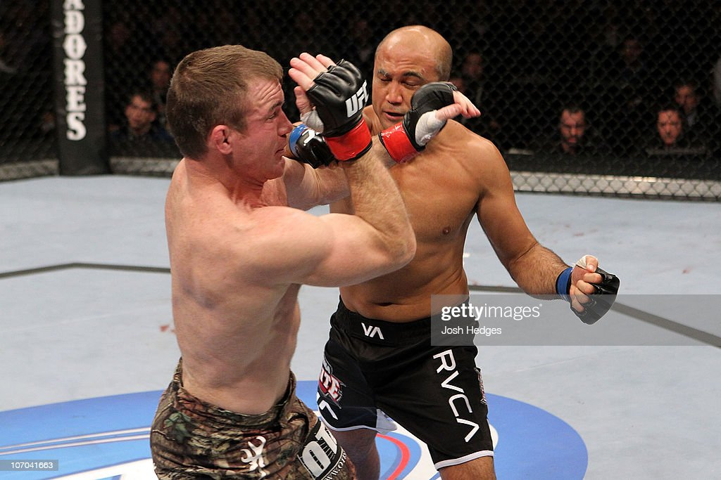 BJ Penn (black trunks/Blue Gloves) knocks down Matt Hughes (red gloves) in the first round during their Welterweight bout part of UFC 123 at the Palace of Auburn Hills on November 20, 2010 in Auburn Hills, Michigan.
