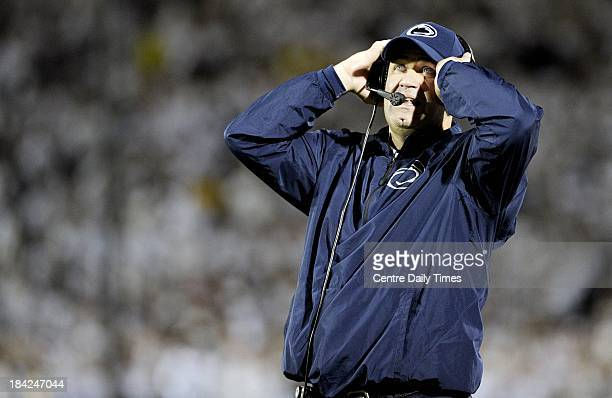 Penn State head coach Bill O'Brien covers his ears to talk through his headset over the noise of the fans during action against Michigan at Beaver...
