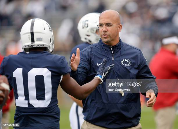 Penn State head coach James Franklin shakes hands with give five and hugs Penn State WR Brandon Polk during warm ups during a college football game...