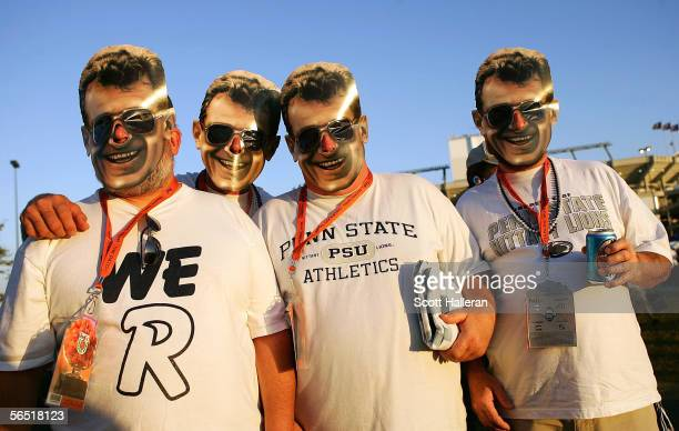 Penn State Nittany Lions fans pose with head coach Joe Paterno masks as they tailgate prior to the start of the FedEx Orange Bowl between the Penn...