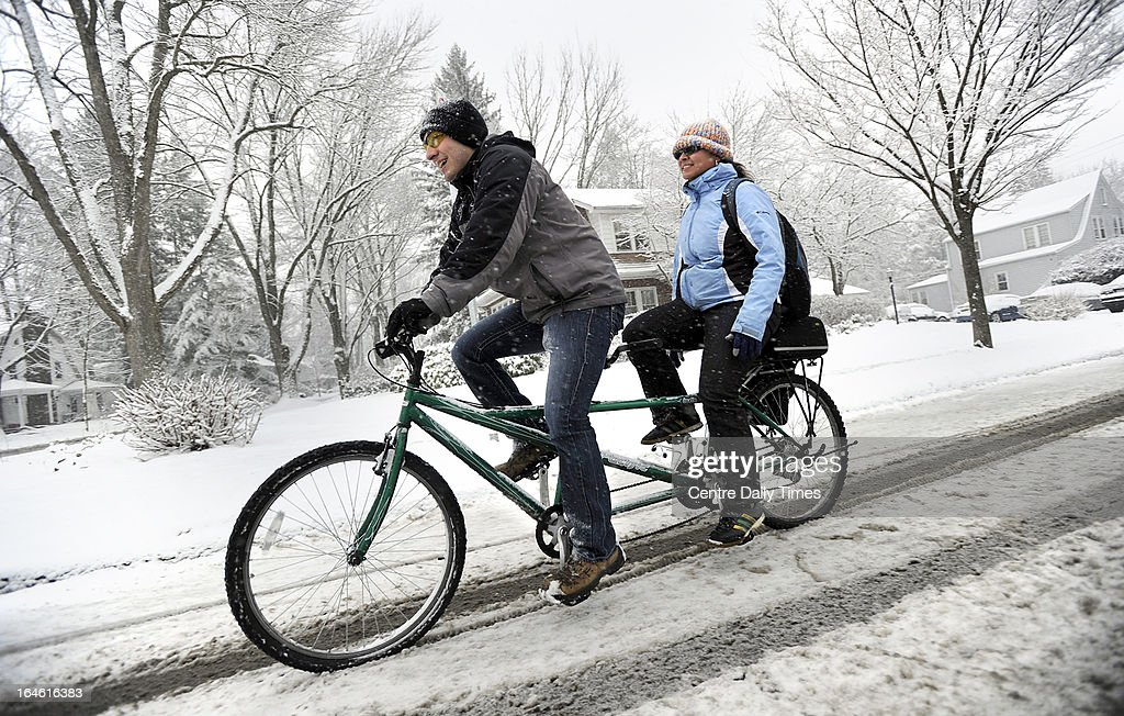 Penn State students David Leinbach, left, and Samantha Rosado ride a tandem bicycle to campus along N Allen Street, in State College, Pennsylvania. Heavy snow fell throughout Centre County, Monday, March 25, 2013, causing local schools to be closed and hazardous traveling conditions.