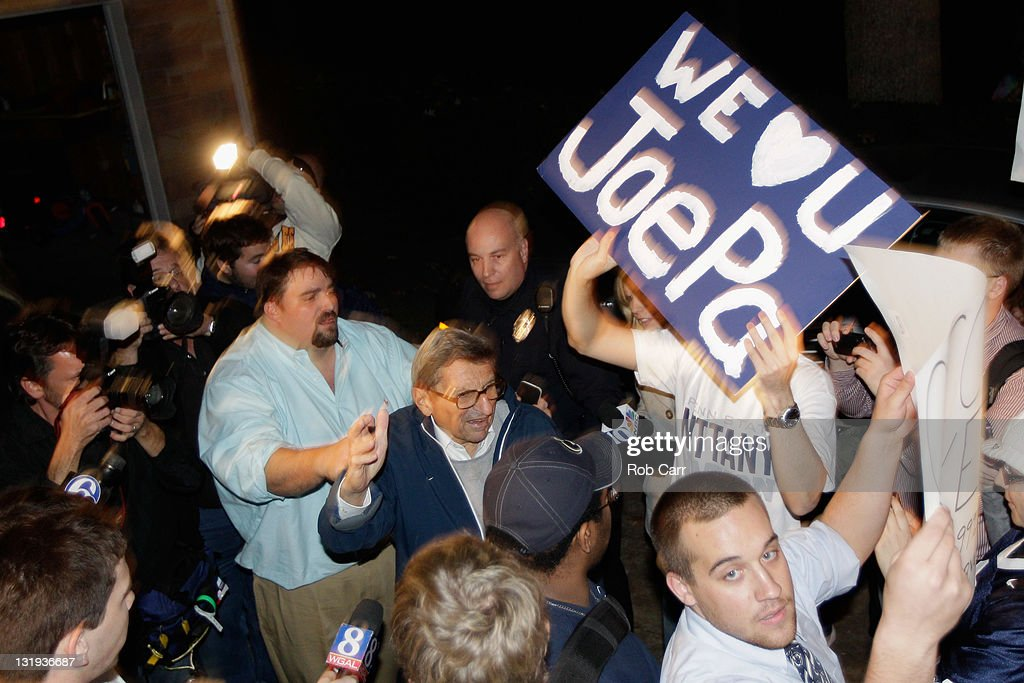Penn State University head football coach Joe Paterno (C) is greeted by a large group of students after arriving at his home, November 8, 2011 in State College, Pennsylvania. Behind Paterno is his son Scott Paterno