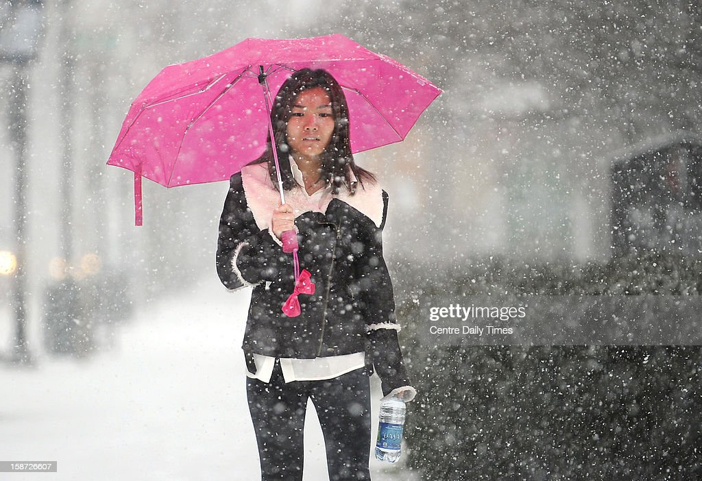 Penn State University student Siyi Sun walks along campus in State College, Pennsylvania, Wednesday, December 26, 2012, as heavy snow falls.