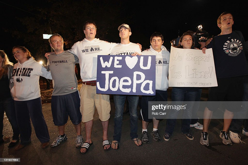 Penn State University students sing outside of the home of head football coach Joe Paterno during November 8, 2011 in State College, Pennsylvania. Behind Paterno is his son Scott Paterno
