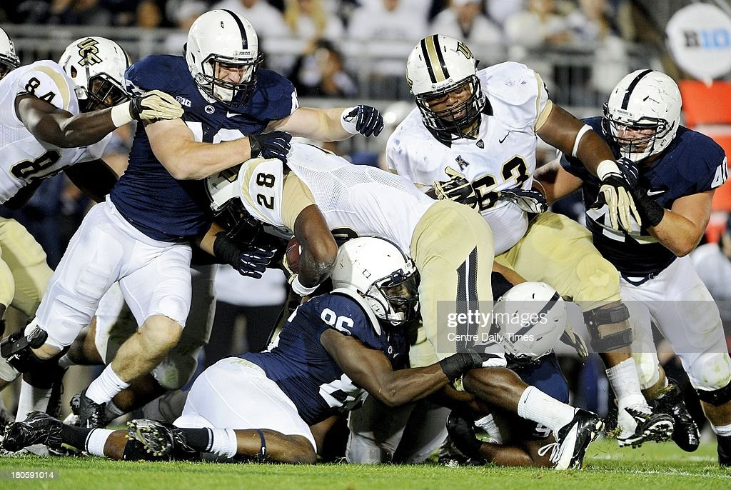 Penn State's C.J. Olaniyan takes down Central Florida ball carrier William Stanback (28) on Saturday, September 14, 2013, at Beaver Stadium in University Park, Pennsylvania. UCF prevailed, 34-31.