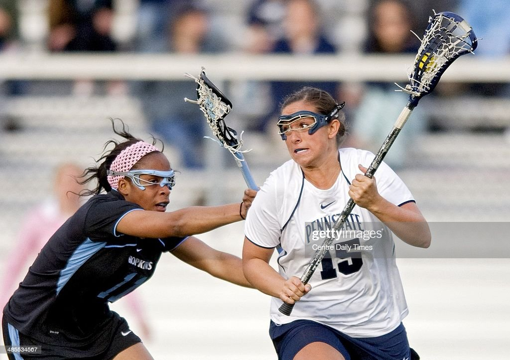 Penn State's Mackenzie Cyr (15) runs with the ball around Johns Hopkins' Octavia Williams during the first half in State College, Pa., Friday, April 18, 2014.