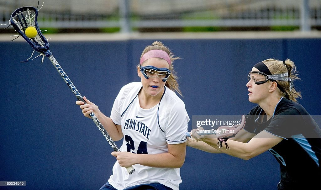 Penn State's Maggie McCormick, left, runs with the ball around John Hopkin's Liz Johnson during the first half in State College, Pa., Friday, April 18, 2014.