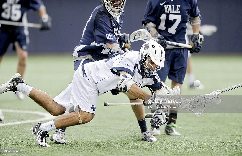 Penn State's Nick Dolik falls as he battles for the ball with Yale defenders during fourth period of the game in the first round of the NCAA men's lacrosse tournament in State College, Pennsylvania, Saturday, May 11, 2013.