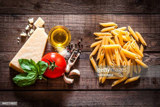 Penne pasta with ingredients on rustic wooden table