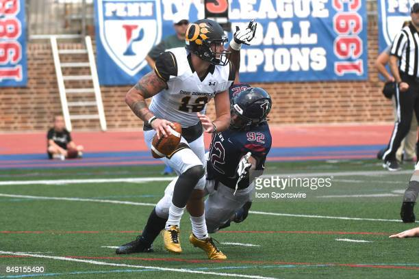 Pennsylvania Quakers defensive end Louis Vecchio attempts to tackle Ohio Dominican Panthers quarterback Grant Russell during a college football game...