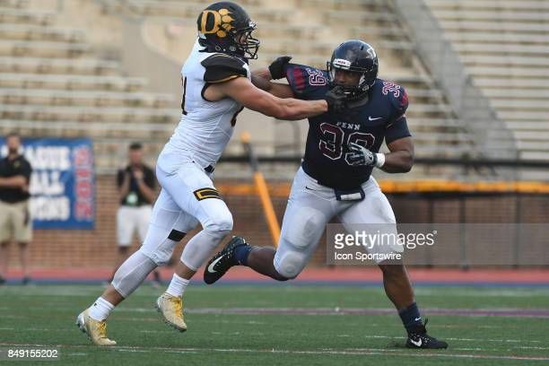 Pennsylvania Quakers linebacker Brandon Mills is blocked by Ohio Dominican Panthers running back Robert Williams during a college football game...