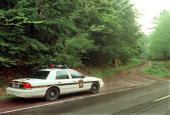 Pennsylvania State Police Trooper guards the entrance to a service road leading to the area of the crash site of a twin engine aircraft that crashed...