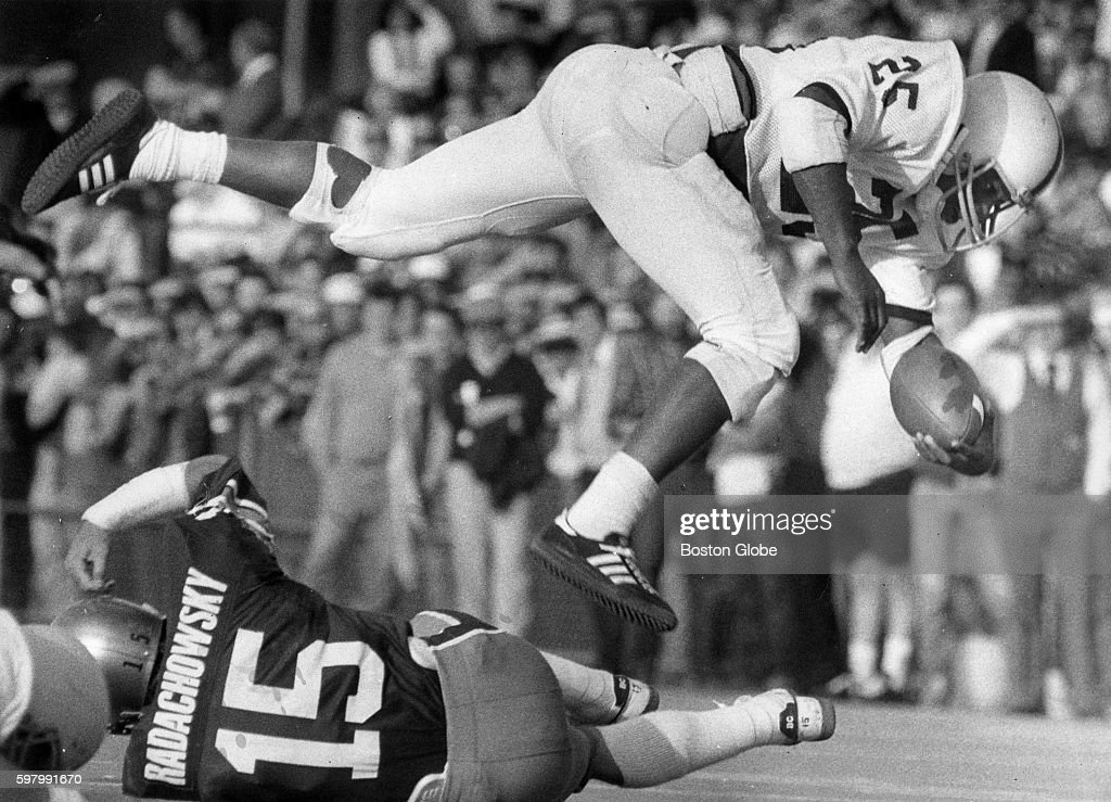 Pennsylvania State University player Curt Warner top flies through the air after tripping over Boston College player George Radachowsky during a game...