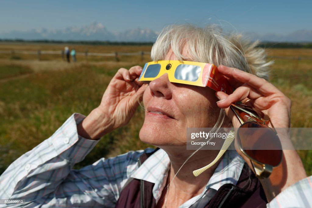Penny Farster-Narlesky of Denver Colorado test her solar eclipse glasses at an roadside information center in Grand Teton National Park on August 20, 2017 outside Jackson, Wyoming. People are flocking to the Jackson and Teton National Park area for the 2017 solar eclipse which will be one of the areas that will experience a 100% eclipse on Monday August 21, 2017.