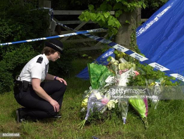WPC Penny Misselbrook from Borehamwood looking at tributes by the scene of Anne Cook's murder near the M1 in Hertfordshire Police are hunting the...