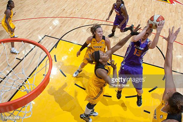 Penny Taylor of the Phoenix Mercury drives to the hoop against Kayla Pedersen Amber Holt and Liz Cambage of the Tulsa Shock during the WNBA game on...