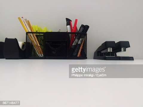 Pens And Staplers Arranged On Table Against Wall