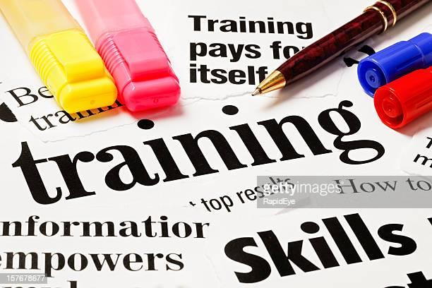 Pens sit on print headlines about skills training