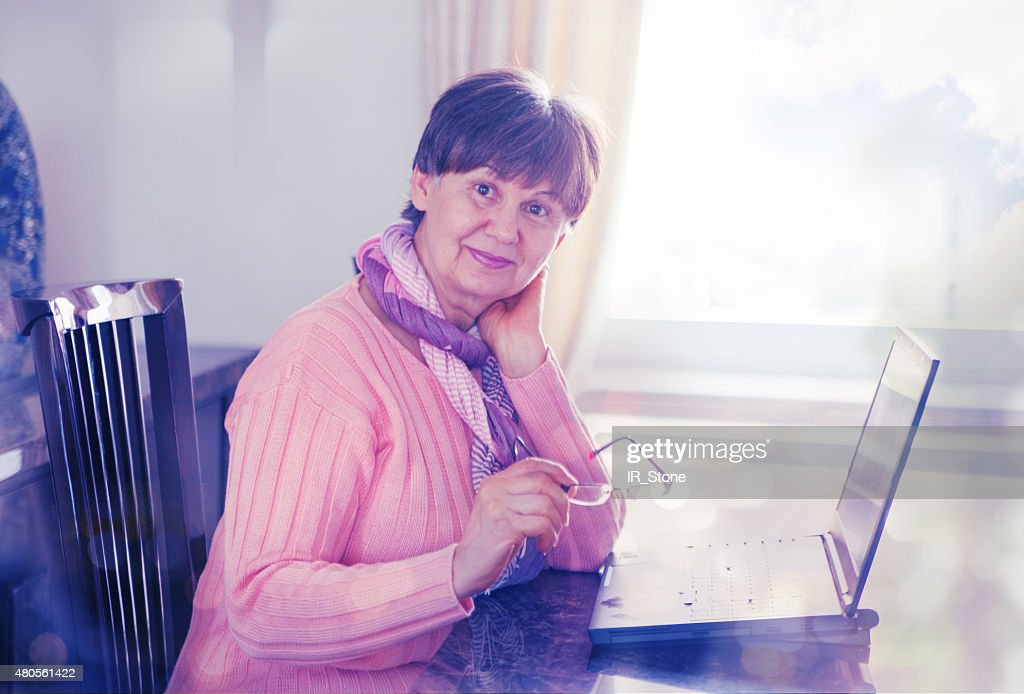 Pension age woman working on laptop : Stock Photo