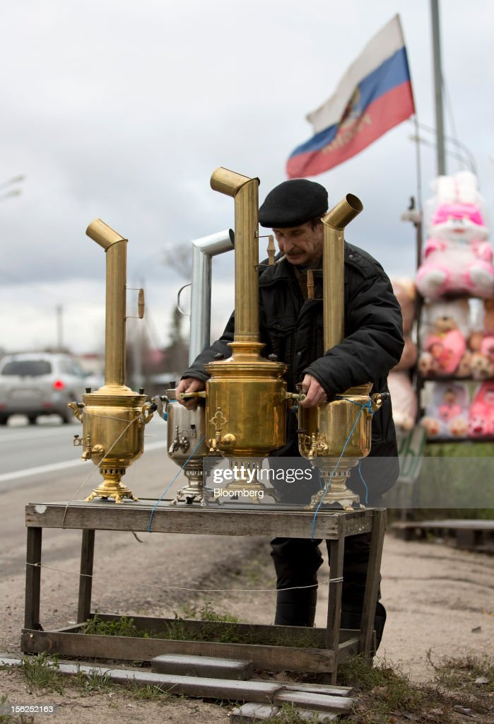A pensioner arranges a display of samovar water heaters for sale on his stall beneath a Russian national flag on the M7 Volga highway outside Ozherelki village, Moscow region, Russia, on Saturday, Nov. 10, 2012. Russia has one of the world's lowest retirement ages, set in 1932 during the Stalin era. Photographer: Andrey Rudakov/Bloomberg via Getty Images