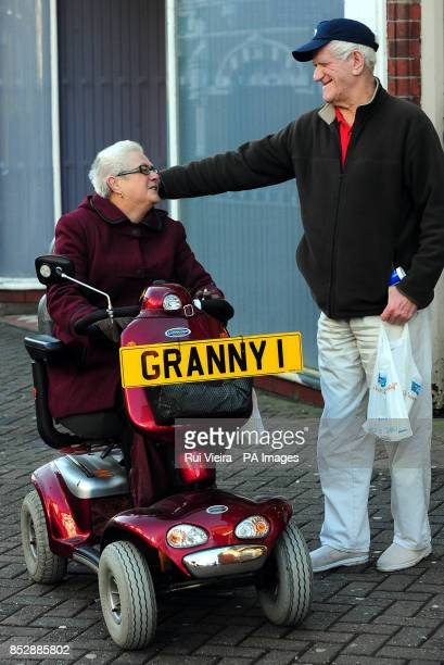 Pensioner Barbara Thompson is greeted by a friend while riding her mobility scooter with a granny plate in South Derbyshire