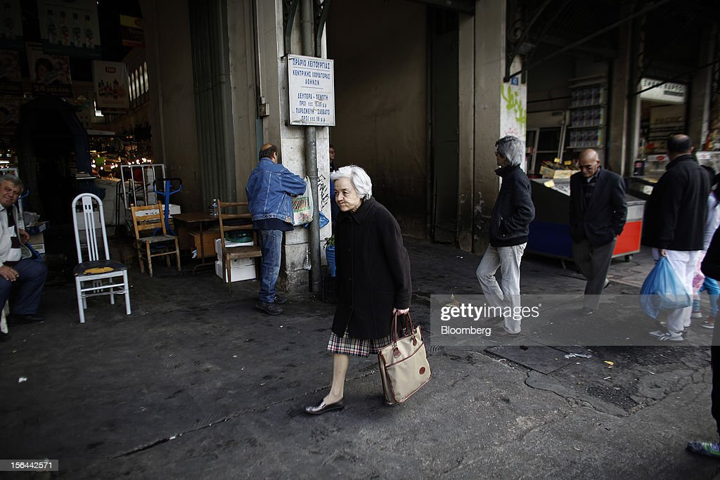 A pensioner carries a shopping bag past the central meat and fish market in Athens, Greece, on Thursday, Nov. 15, 2012. Greece's Supreme Court of Audit ruled that Greek austerity measures including cuts to pensions and an increase in the retirement age may be unconstitutional, state-run Athens News Agency reports, without citing anyone. Photographer: Kostas Tsironis/Bloomberg via Getty Images