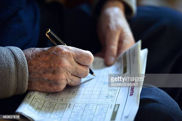 A pensioner fills in the crossword prior to Christmas eve dinner on December 24 at the St Joseph retirement home in Nantes AFP PHOTO/GEORGE GOBET