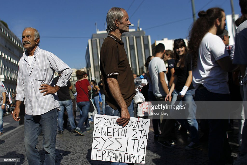 A pensioner holds a placard reading 'Pensioners and unemployed at soup kitchens, proud elderly men' during a general strike protest in Athens, Greece, on Tuesday, Nov. 6, 2012. Greece headed for a cliffhanger vote on austerity measures needed to keep the bailout on track as a 48-hour general strike began and European officials squabbled over the timing of a deal to unlock rescue funds. Photographer: Kostas Tsironis/Bloomberg via Getty Images