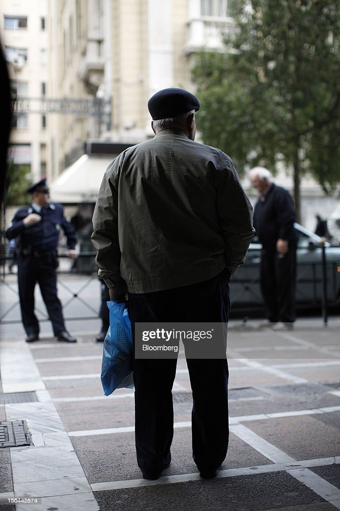 A pensioner holds a shopping bag as he stands and protests against pension cuts outside the shuttered entrance to the Labor ministry in Athens, Greece, on Thursday, Nov. 15, 2012. Greece's Supreme Court of Audit ruled that Greek austerity measures including cuts to pensions and an increase in the retirement age may be unconstitutional, state-run Athens News Agency reports, without citing anyone. Photographer: Kostas Tsironis/Bloomberg via Getty Images
