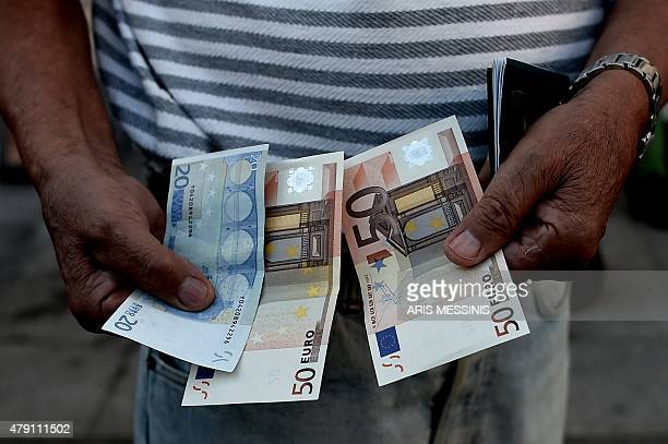 A pensioner holds banknotes next to people waiting outside a national Bank branch as banks only opened for pensioners to allow them to cash out up to...