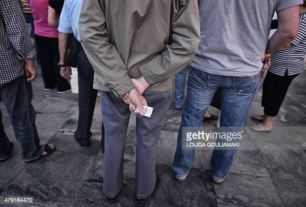 A pensioner holds his priority ticket as he waits outside the National bank of Greece headquarters to get his pension on July 2 2015 Nearly one in...