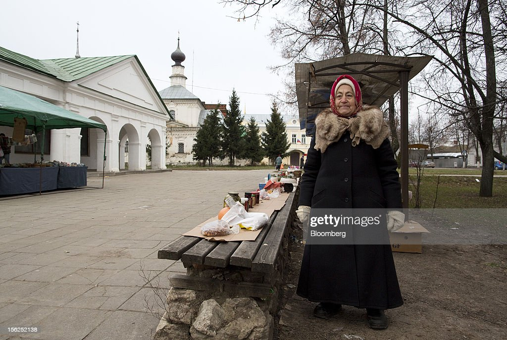 A pensioner poses for a photograph beside her street stall selling food produce in Suzdal, Russia, on Saturday, Nov. 10, 2012. Russia has one of the world's lowest retirement ages, set in 1932 during the Stalin era. Photographer: Andrey Rudakov/Bloomberg via Getty Images