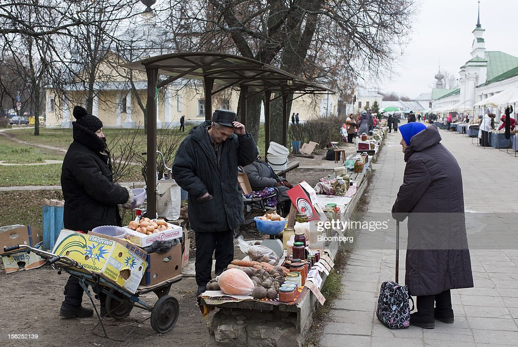 A pensioner, right, speaks to traders selling food produce at their street stall in Suzdal, Russia, on Saturday, Nov. 10, 2012. Russia has one of the world's lowest retirement ages, set in 1932 during the Stalin era. Photographer: Andrey Rudakov/Bloomberg via Getty Images