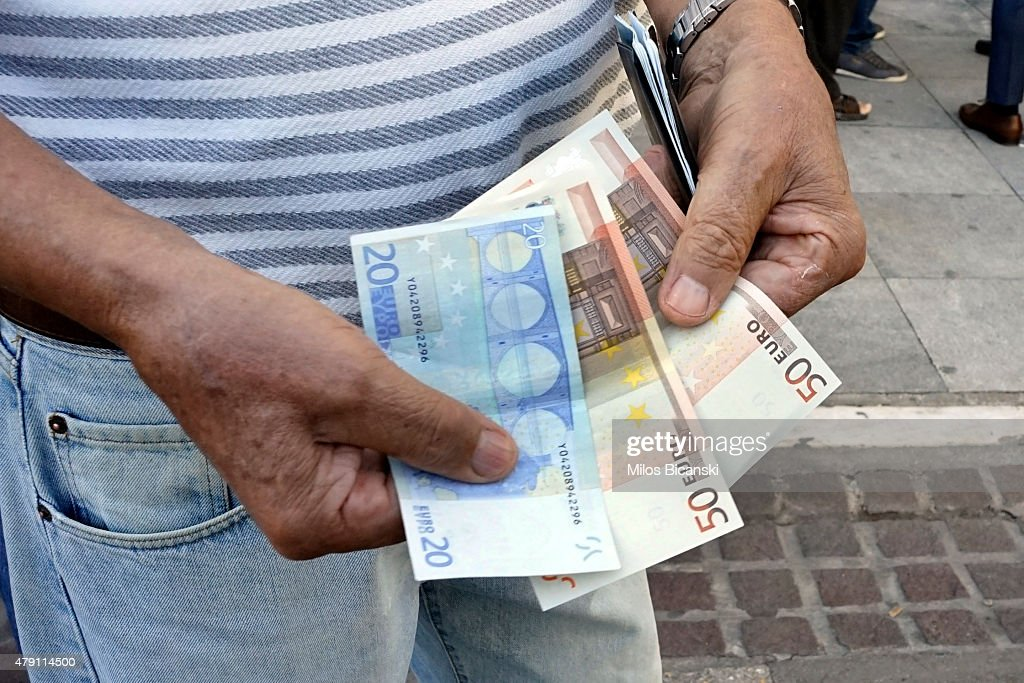 A pensioner shows the part of his pension he received on July 1 2015 in Athens Greece Bank branches around Greece are opened on Wednesday to allow...