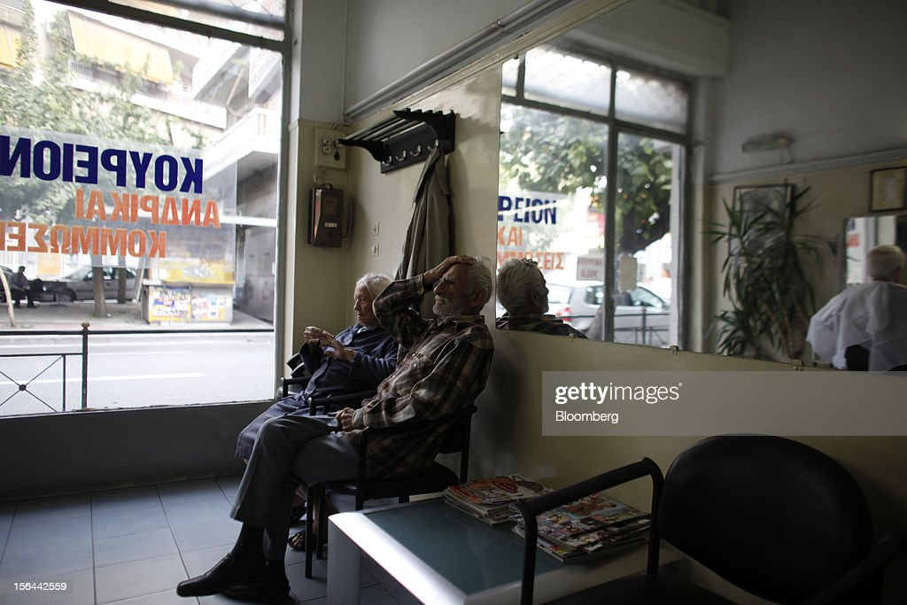 A pensioner sits with his wife and waits for a haircut inside a barber's shop in Athens, Greece, on Thursday, Nov. 15, 2012. Greece's Supreme Court of Audit ruled that Greek austerity measures including cuts to pensions and an increase in the retirement age may be unconstitutional, state-run Athens News Agency reports, without citing anyone. Photographer: Kostas Tsironis/Bloomberg via Getty Images