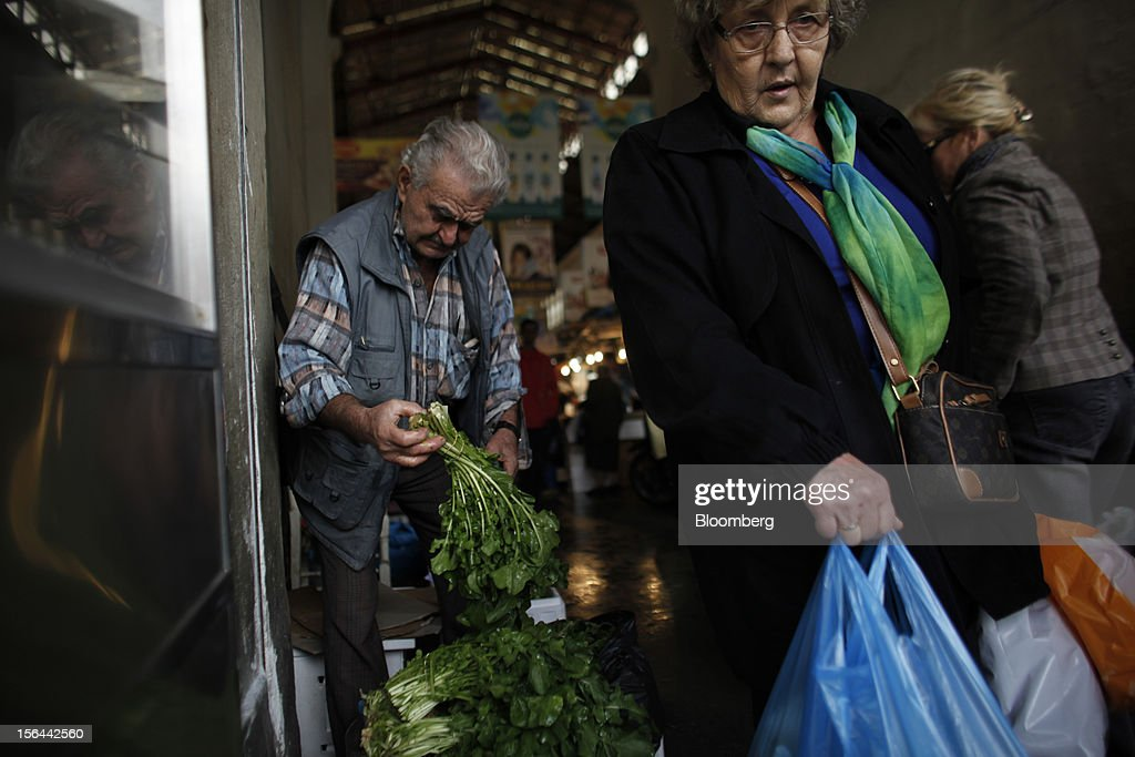 A pensioner stands and sells vegetables which he collects from the outskirts of the city to customers in the central meat and fish market in Athens, Greece, on Thursday, Nov. 15, 2012. Greece's Supreme Court of Audit ruled that Greek austerity measures including cuts to pensions and an increase in the retirement age may be unconstitutional, state-run Athens News Agency reports, without citing anyone. Photographer: Kostas Tsironis/Bloomberg via Getty Images