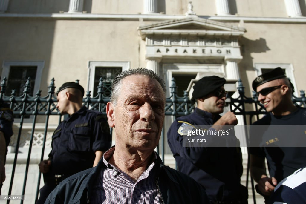 A pensioner stands in front riot police officers during a rally against new pension cuts, outside the Counsel of State, the Supreme Administrative Court of Greece, in Athes on October 6, 2017