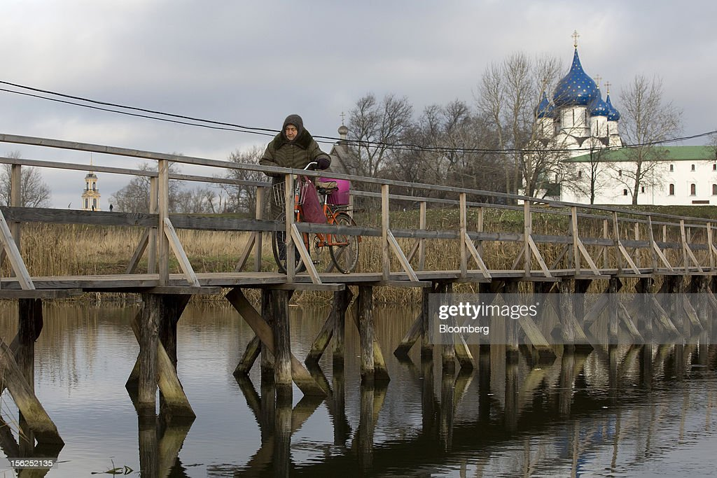 A pensioner wheels her bicycle across a wooden bridge on the Kamenka river in Suzdal, Russia, on Sunday, Nov. 11, 2012. Russia has one of the world's lowest retirement ages, set in 1932 during the Stalin era. Photographer: Andrey Rudakov/Bloomberg via Getty Images