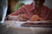 Close up of hand pensioner woman calculating.