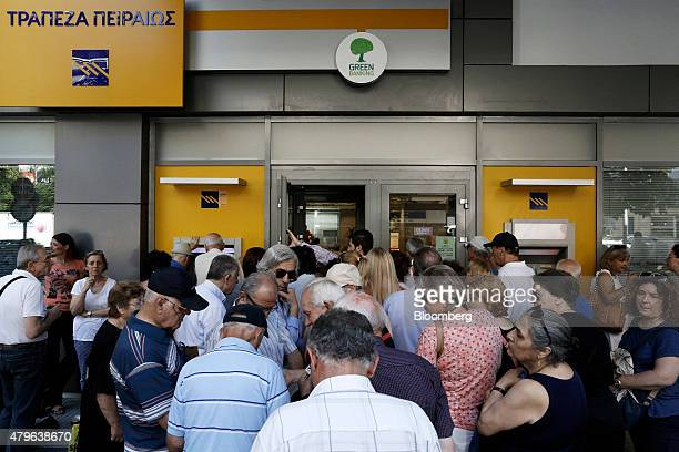 Pensioners and customers wait to withdraw cash from an automated teller machine as they queue outside a Piraeus Bank SA bank branch in Thessaloniki...
