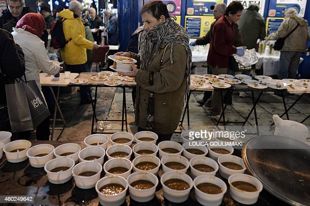 Pensioners get a bowl of hot soup outside the Finance Ministry in Athens late on December 10 as they participate in a nightlong protest against the...